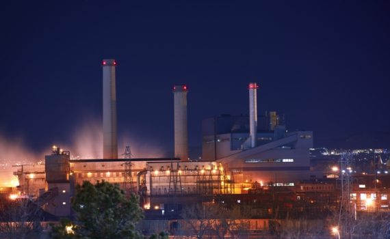 Industrial Zone at Night. Industrial Buildings Illumination and Smoke.